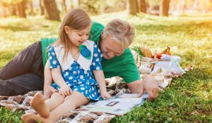 Kindergartener reads magazine with her father