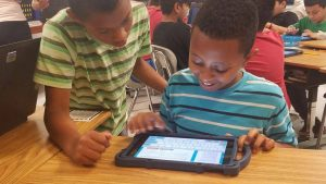 Two elementary students learning on a tablet